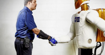 Marty Linn, General Motors manager of advanced technology and principal engineer for robotics, shakes hands with Robonaut 2 (R2), a humanoid robot developed by GM and NASA during a nine-year collaboration that also led to the development of the RoboGlove, an exo-muscular devices that enhances strength and grip through leading-edge sensors, actuators and tendons that are comparable to the nerves, muscles and tendons in a human hand.