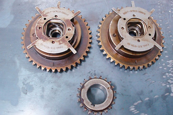 These camshaft sprockets and timing gears are integral parts on this Ford application. The stamped steel plates are reluctors that allow the camshaft position sensor to sense valve timing. A conventional timing chain sprocket completes the set.